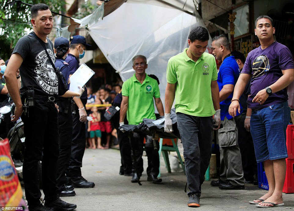 Authorities carry a dead man killed in the violent drug raids in the Philippines