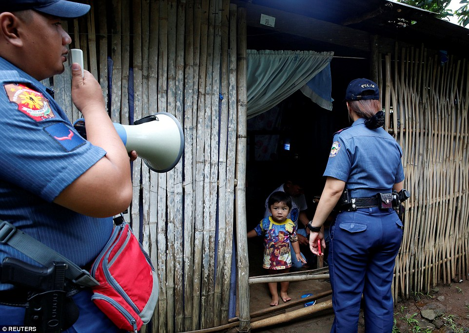 Police look to enter a house to take a grandfather to a police station as part of the crackdown