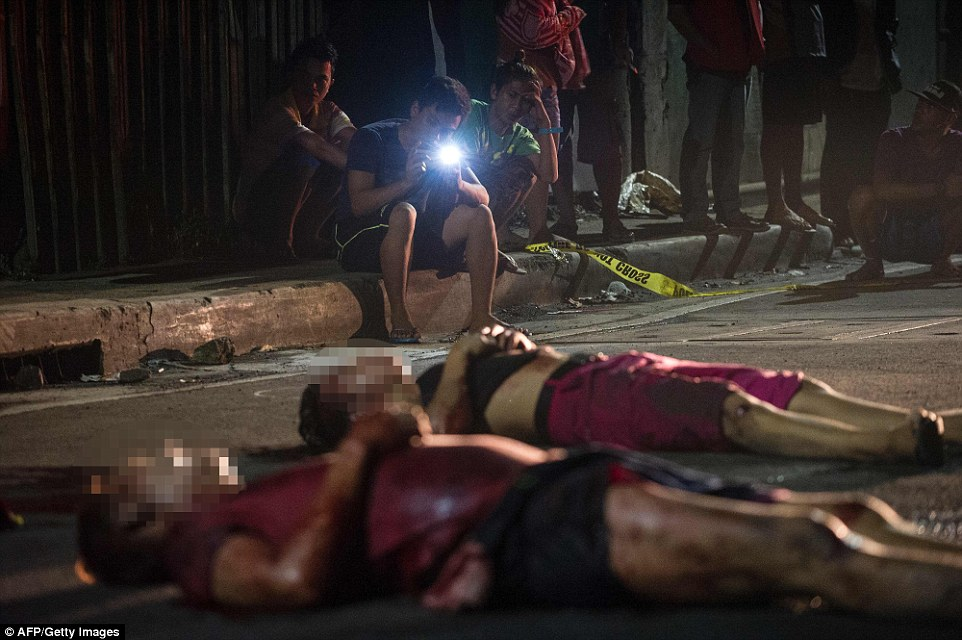 A young man takes a photo of two victims of the violent drug war that has claimed more than 3,700 people according to reports