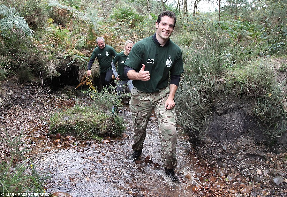 Happy chappy: Henry gave the thumbs up as he waded through a stream with his team close behind him
