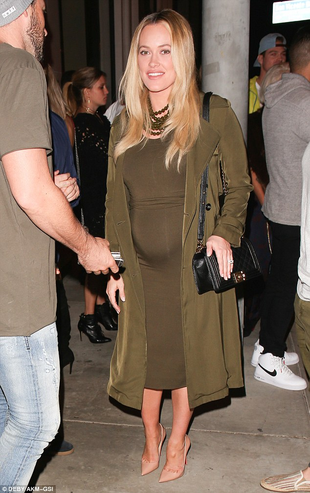 She's glowing: The New Zealand-born beauty showcased her growing baby bump in an olive green curve-hugging dress which fell below her knees