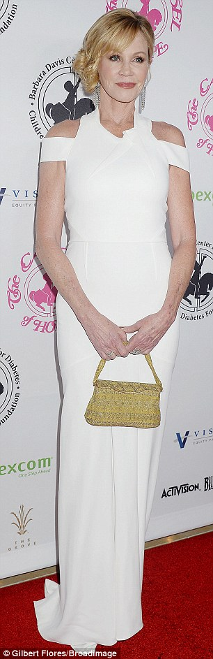 Flawless: The actress added a beaded mustard purse and coral lipstick to round out her look