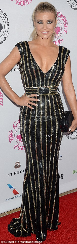 Sparkling: Carmen Electra showed off her incredible curves in a skintight black and gold v-neck dress