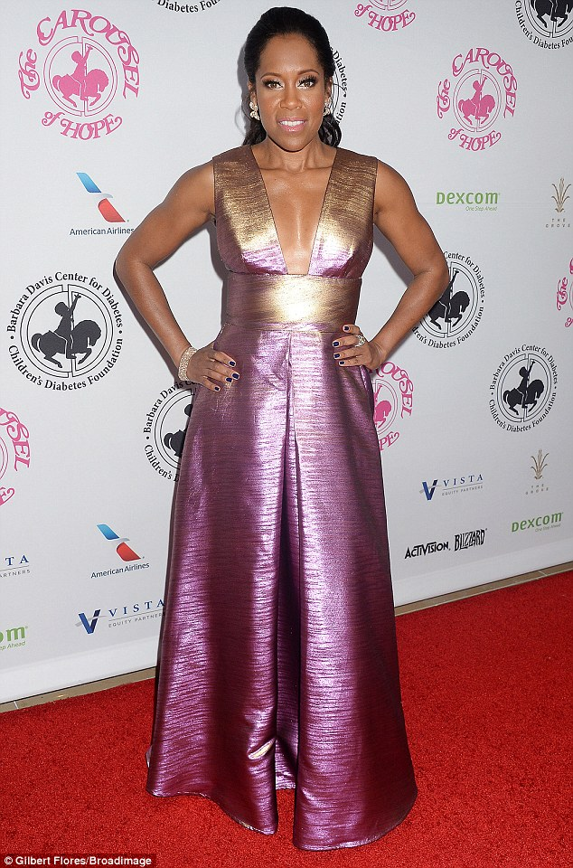 Sparkling: Regina King, 45, slipped on a gold and purple shimmering dress that had a plunging neckline and cinched waist