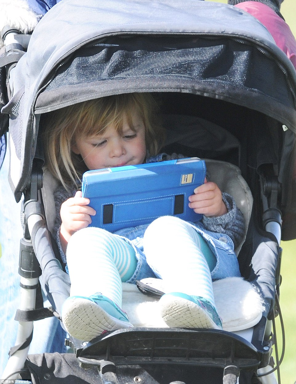 Mia was spotted engrossed in her iPad while her mother took part in a riding event on Sunday
