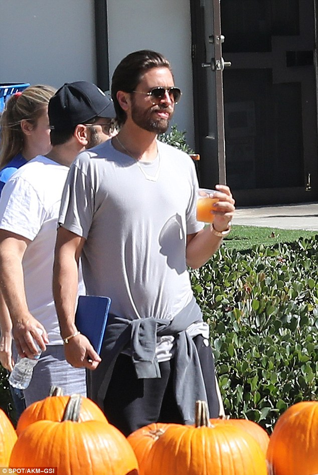 Yum: Scott quenched his thirst as he carried a cool beverage while strolling through the patch