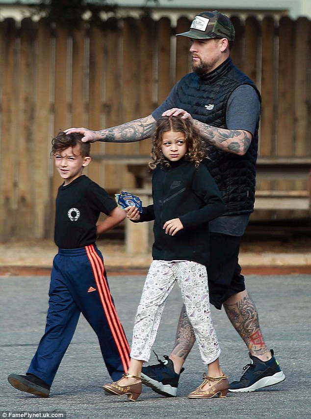 Protective pops: Madden, seen here last month in Los Angeles with the kids, keeps a hand on both of his tots