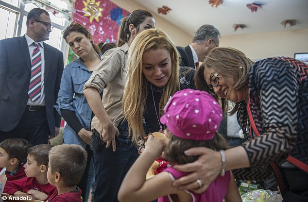 Meeting the refugees: The Parent Trap star, 30, flashed a beaming grin to the delight of the surrounding aid workers