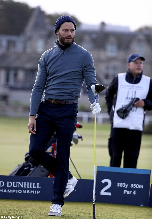 Keep your eye on the ball: The star leaned against his driver on the second tee