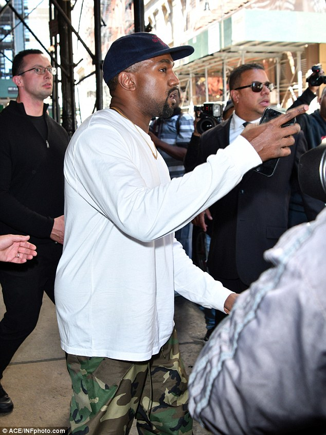 Ramping up security: Kim's hubby Kanye is seen, surrounded by security guards on Friday