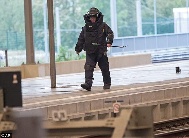 A bomb squad police officer patrols the scene at a station in Chemnitz after a suspicious suitcase was found on a platform