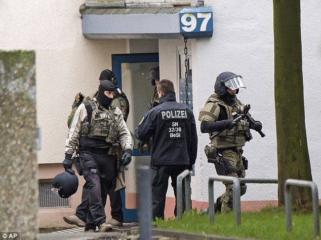 A squad of specialist police officers leave an apartment after carrying out controlled detonations on the Chemnitz estate