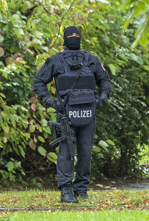 An armed police officer stands on guard during patrols of the estate in Chemnitz yesterday