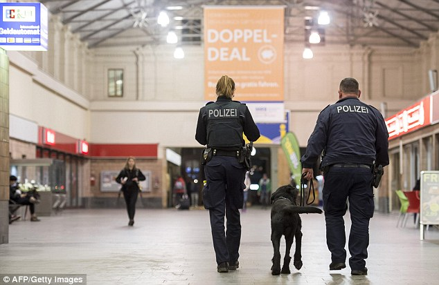 Police officers with a search dog patrol a station in Chemnitz after a suitcase was found on a platform yesterday