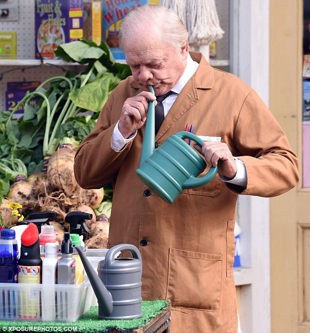 Working up a sweat: Armed with a turnip and watering can, David was in high spirits as he got stuck into scenes dressed in his character's white shirt, tie and dark brown slacks