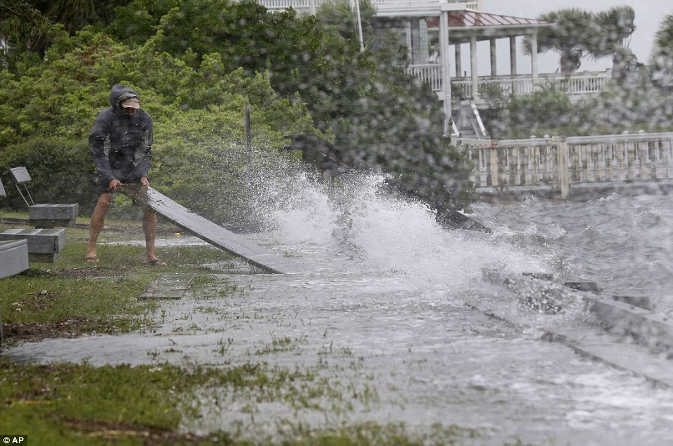 In Wrightsville Beach, a resident dislodged timber from an overflowing seawall as waves continued to grow in height