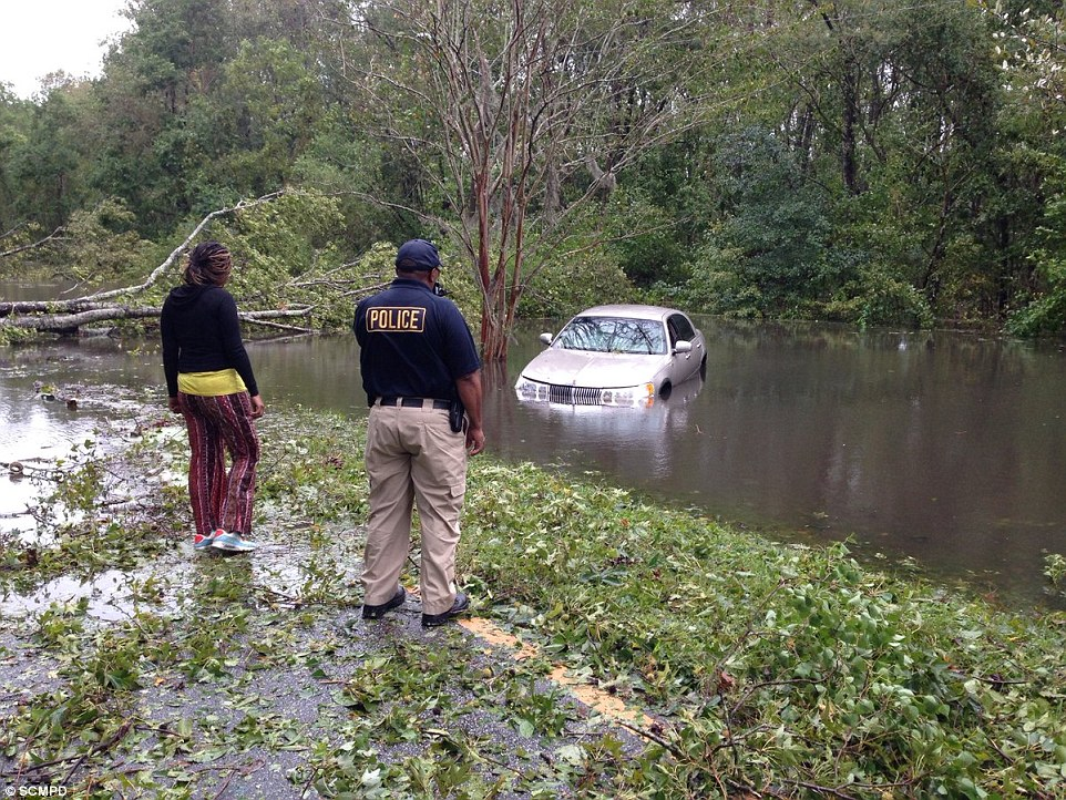 In Savannah, Georgia, police assist a woman as she surveys her flooded car after the storm passed through the state