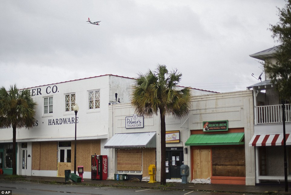 A U.S. Coast Guard plane flies over boarded up shops after Hurricane Matthew passed through St. Simons Island