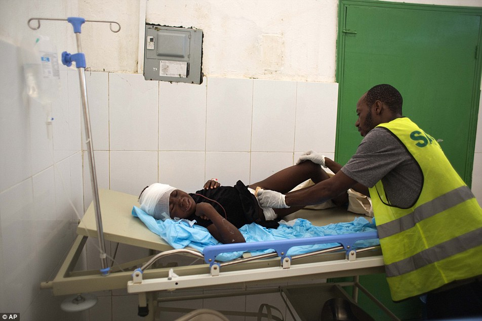 Dr Ronsard Presandieu helps Theodor Florine, 8, at the state hospital after the Hurricane Matthew, in Jeremie, Haiti, one of the areas that was hit the hardest by Hurricane Matthew earlier this week