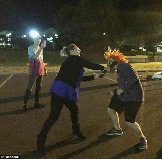 Thisimage shows a woman confronting a clown, hitting him in the face with a long object