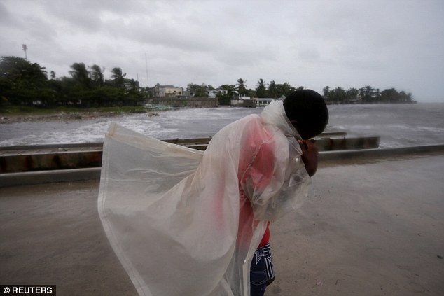 The storm drenched Haiti's south-east coast on Monday, with 430,000 people evacuated. This boy tried to shelter from the rain at Les Cayes, Haiti