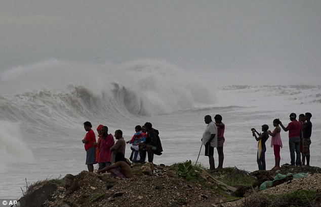 People stand on the coast watching the surf produced by Hurricane Matthew. It is one of the most powerful Atlantic hurricanes in recent history