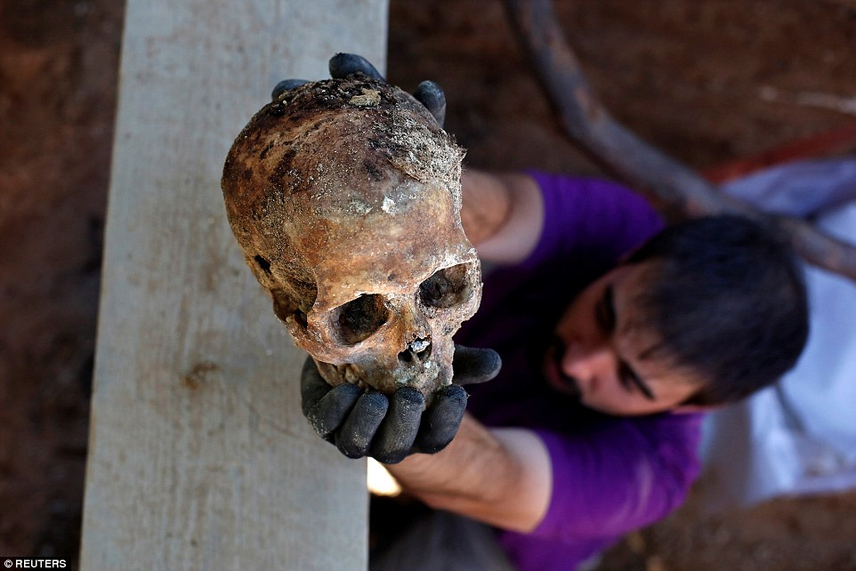 Archaeologist Gonzalo Saiz holds up a human skull which was found buried in an unmarked pit in Valladolid