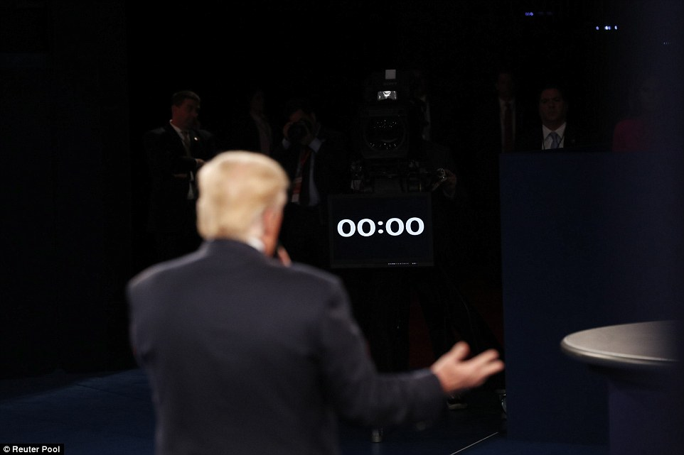 Republican candidate Donald Trump stands on the debate stage as a clock in front of his shows time has run out for an answer