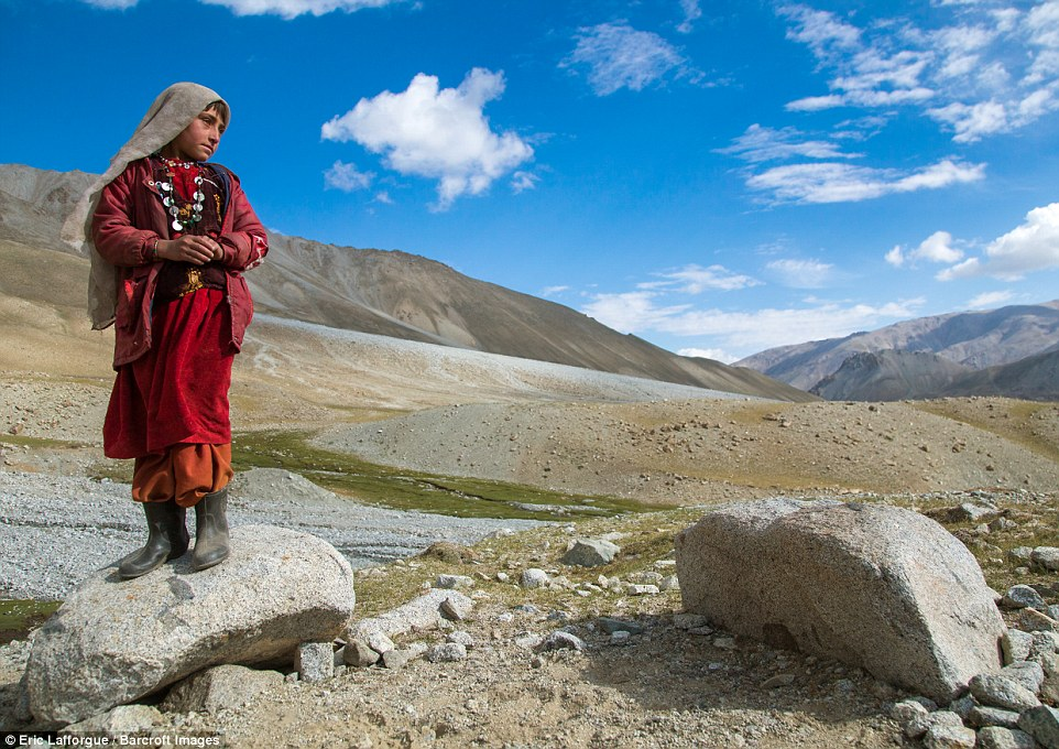 A Wakhi nomad girl stands on a rock as she overlooks the harsh, desolate terrain between Tajikstan and Pakistan