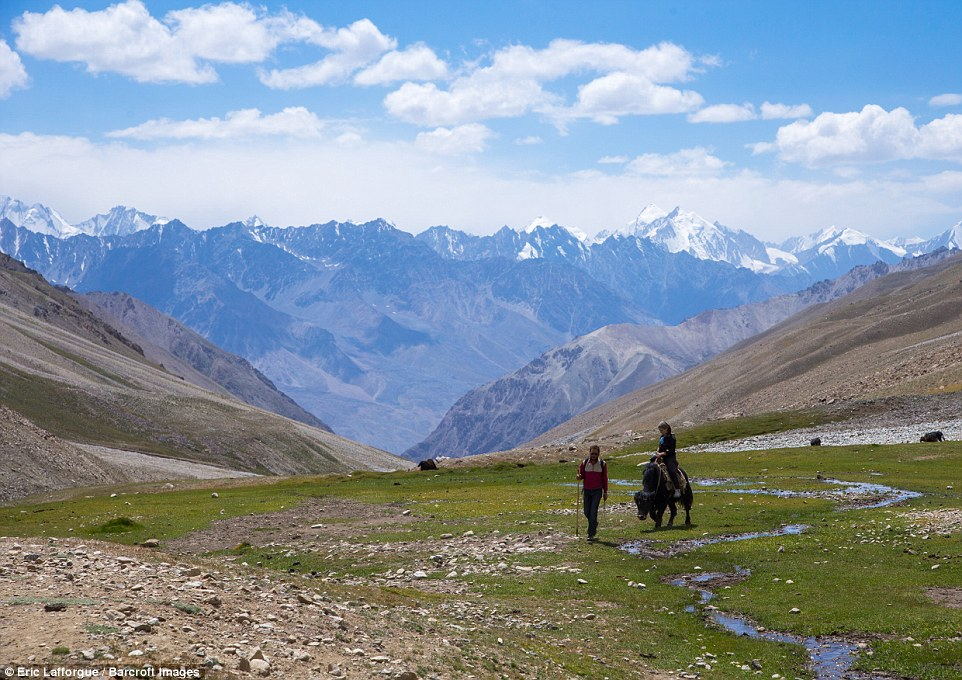 A man and woman take to the trek trail in the Pamir mountains with yaks. The tourist season ended shortly after the photographer's visit as snow was due to fall
