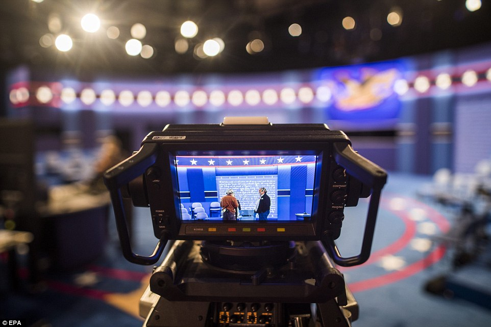 Workers put the finishing touches on the debate stage where students have been helping to prep the stage at Washington University