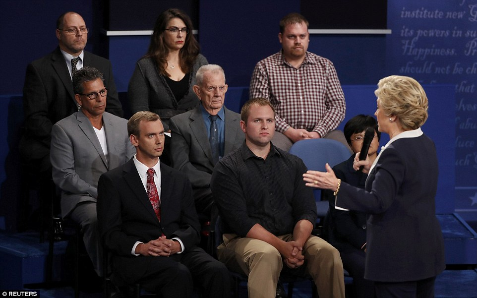 Members of the audience look on on Hillary Clinton speaks to them and answers a question during the second presidential debate