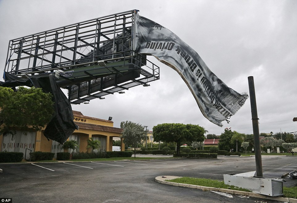 Stripped: A billboard canvas flaps in the wind in North Palm Beach, Florida, after Category 3 Hurricane Matthew passed off shore with top sustained winds of 120mph