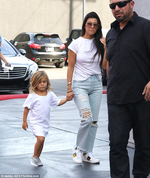 Extra bodyguard: Kourtney added oversized sunglasses and cute sneakers as she stuck close to her new security