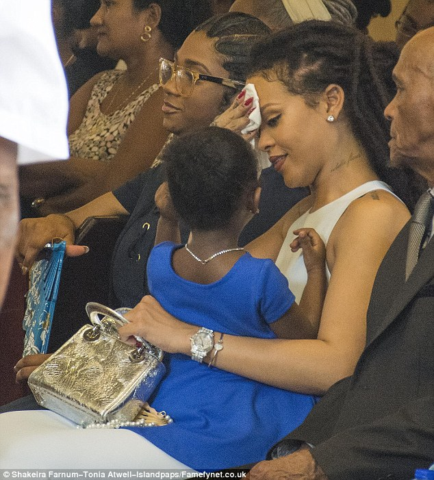 Steaming up: It may have been a bit hot in the church as Rihanna was seen wiping the perspiration from her brow
