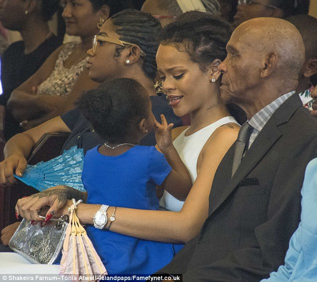Maternal: She played the doting aunt as she entertained the tot during the ceremony
