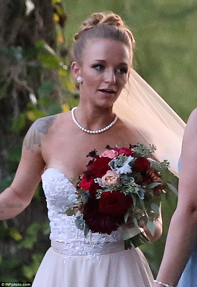 Big day: Maci added a pearl necklace and carried a pretty bouquet of red and pink flowers