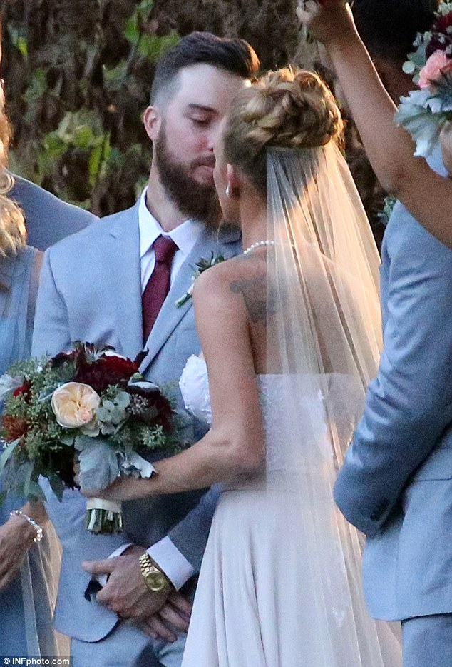 Smooch: The newlyweds moved in for a kiss as they posed for photos with their large wedding party