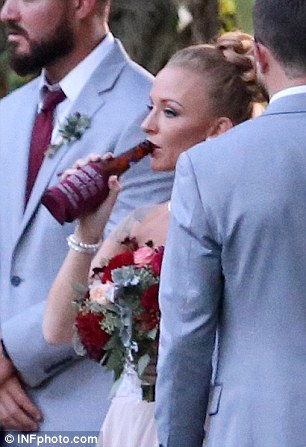 Party time: The bride got a jump on the reception festivities as she grabbed a drink while posing for photos