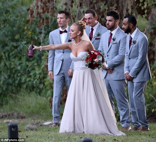 Drink up: The bride offered a sip to some friends as she posed with the groomsmen