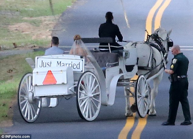 On their way: The couple later headed off in a white  carriage with a 'Just Married' sign