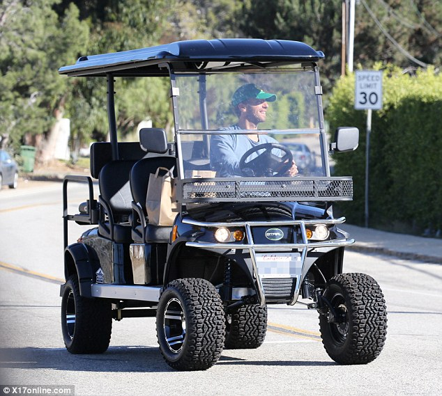 Casual outing: The Coldplay frontman, 39, looked relaxed and joyful as he sported a large smile and a happy face baseball hat and no shoes