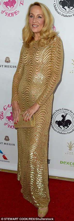 Shining star:Jerry Hall, 60, wowed in a floor-length gold patterned maxi with matching colored heels and purse