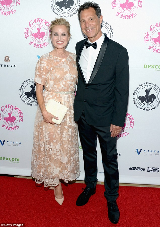 Staying close:Maureen McCormick wore a sheer white and nude floral dress with a sparkling belt cinching her waist; pictured with husband Michael Cummings