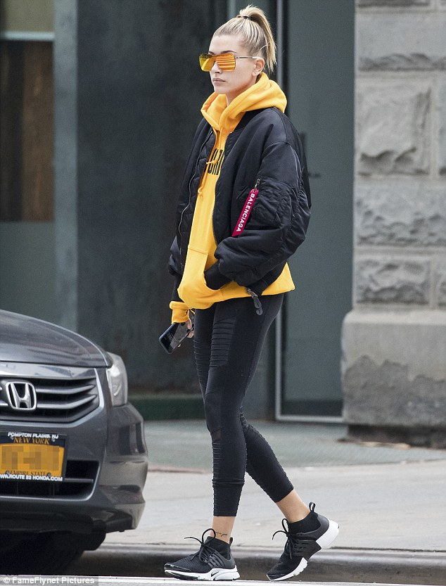 She's a beauty:The 19-year-old bundled up in the tangerine toned hoodie with black leggings and a matching hued bomber jacket