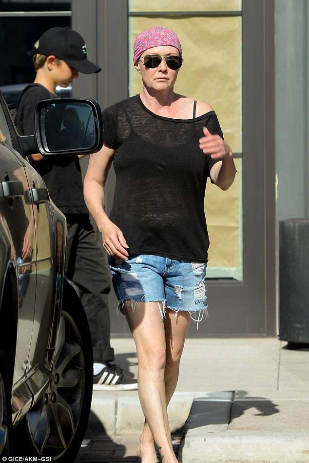 Going strong: The former Beverly Hills 90210 star looked fighting fit in flip flops and cutoff jeans and a black sheer top, protecting her newly-bald head from the sun in a pink do-rag