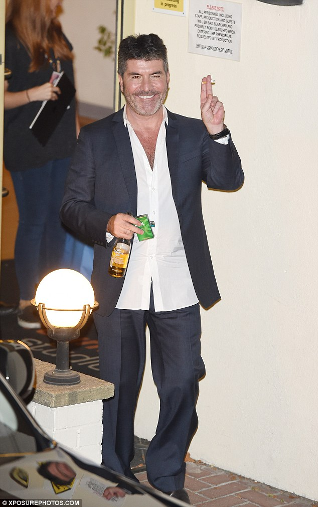The main man: Simon looked to have enjoyed his return to the live arena, exiting with a cigarette and bottle of beer in hand