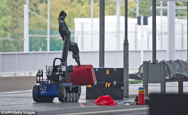 A remote controlled bomb disposal robot lifts a suitcase on a platform of the train station in Chemnitz, eastern Germany on Saturday