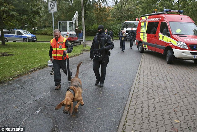 Pictured: A German police dog unit team up with specialist officers to search a housing estate in Chemnitz