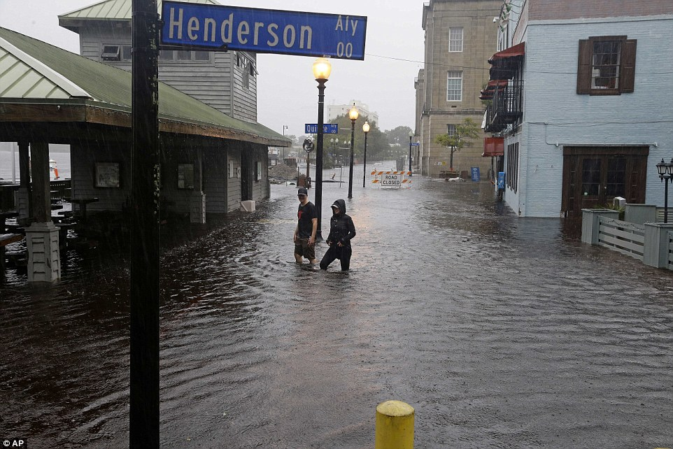 Matthew was downgraded to a post-tropical cyclone just before daybreak Sunday morning but flash floods continue to remain a danger in North Carolina (pictured is Wilmington on Saturday)